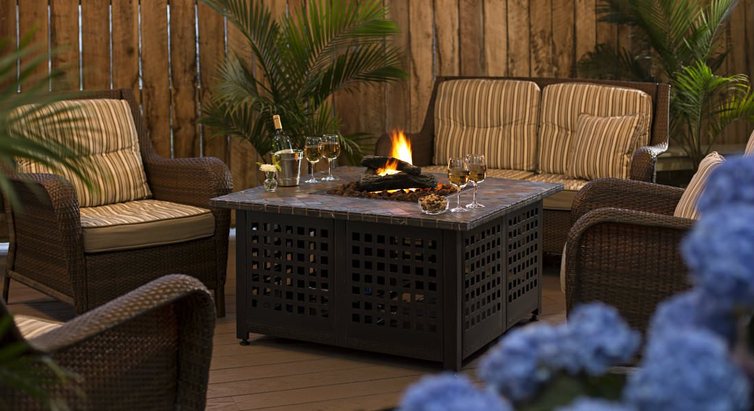 Several brown wicker chairs around a small firepit inside a table.