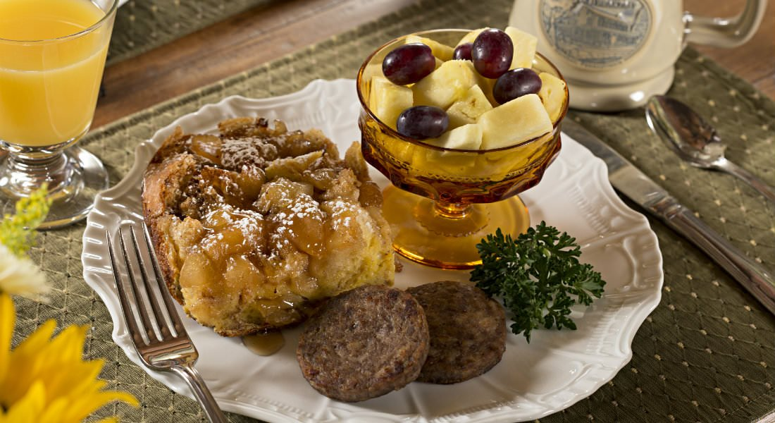 A golden brown french toast casserole frenched in maple syrup with a gold fruit cup of pineapple and purple grapes as well as two sausage patties.