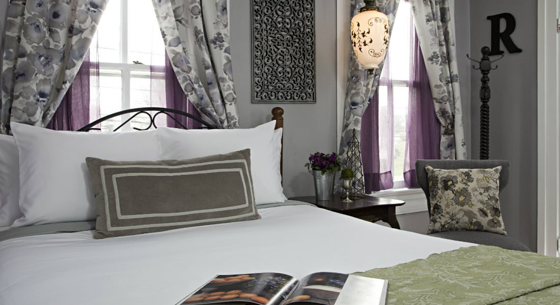 A white and green bed in a grey room with deep purple curtians.