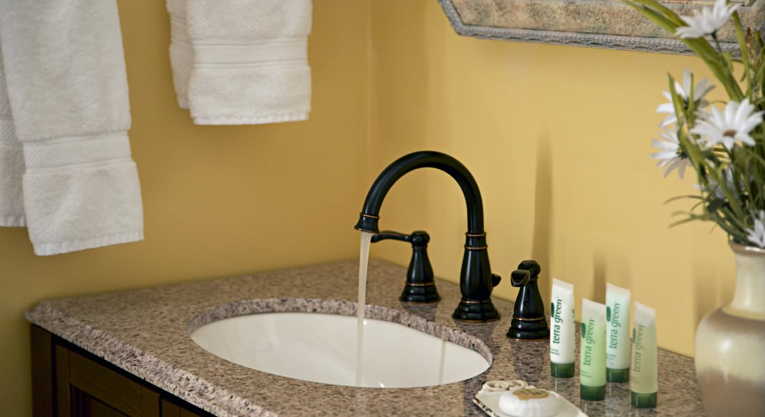 A sink with black faucet in a lemon yellow bathroom.