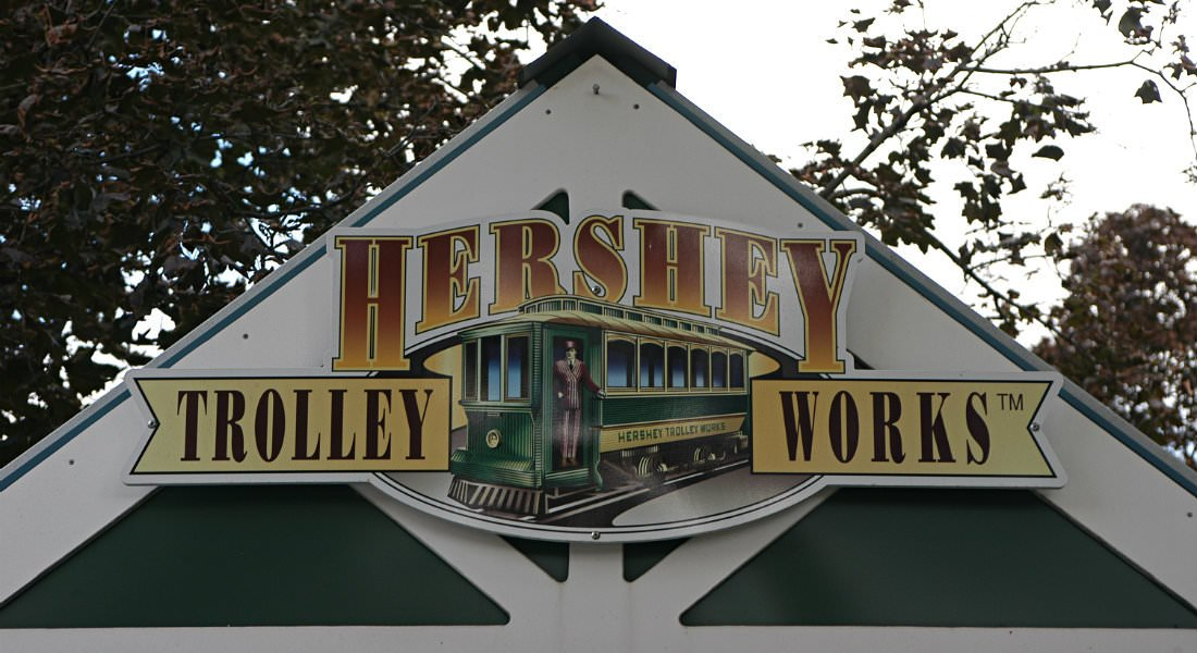 A green and yellow sign advertising Hershey's Trolly Works.