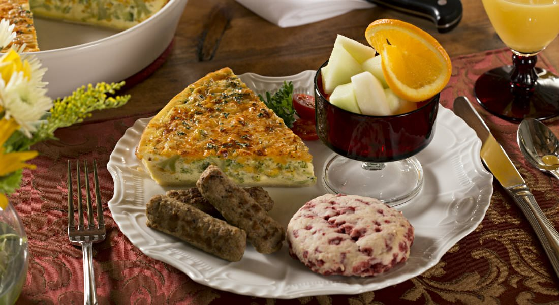 A brekfast plate with a slice of cheese and brocoli quiche, a strawberry pastry, a red fruit cup of green honeydew and oranges, and two links of sausage.