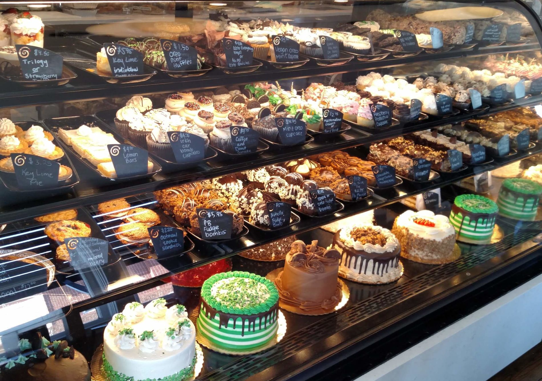 Glass display case with shelves of decadent desserts