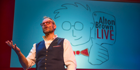 Color photo of foodist Alton Brown with bright blue background and caricature of Mr. Brown for his Alton Brown Live Tour at Hershey Theatre November 2014