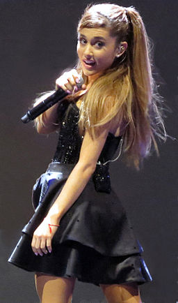 Color photo of Ariana Grande wearing a black dress