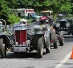 Photograph of very old cars lining up on road