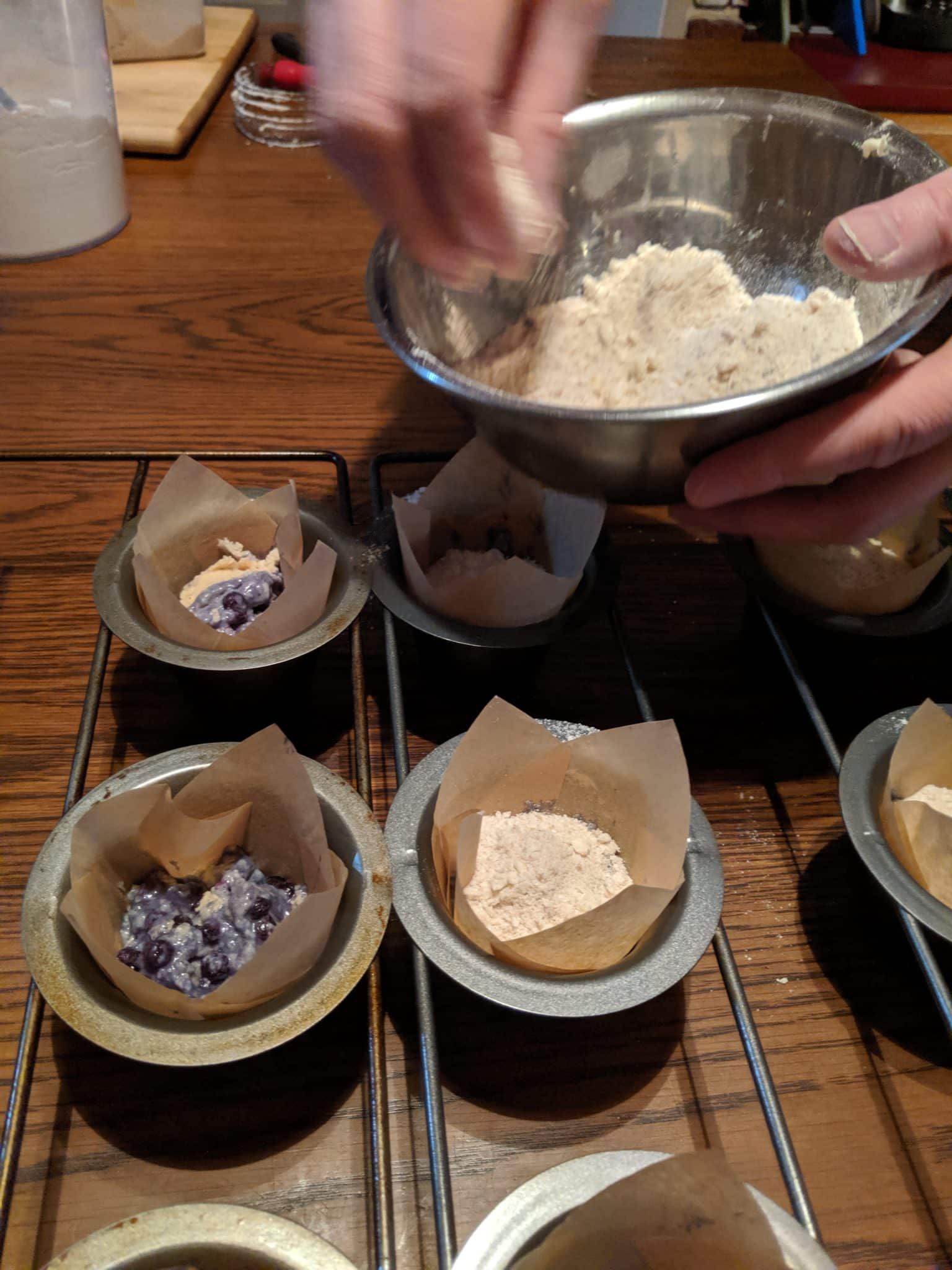 muffin batter in tins with crumb topping being added