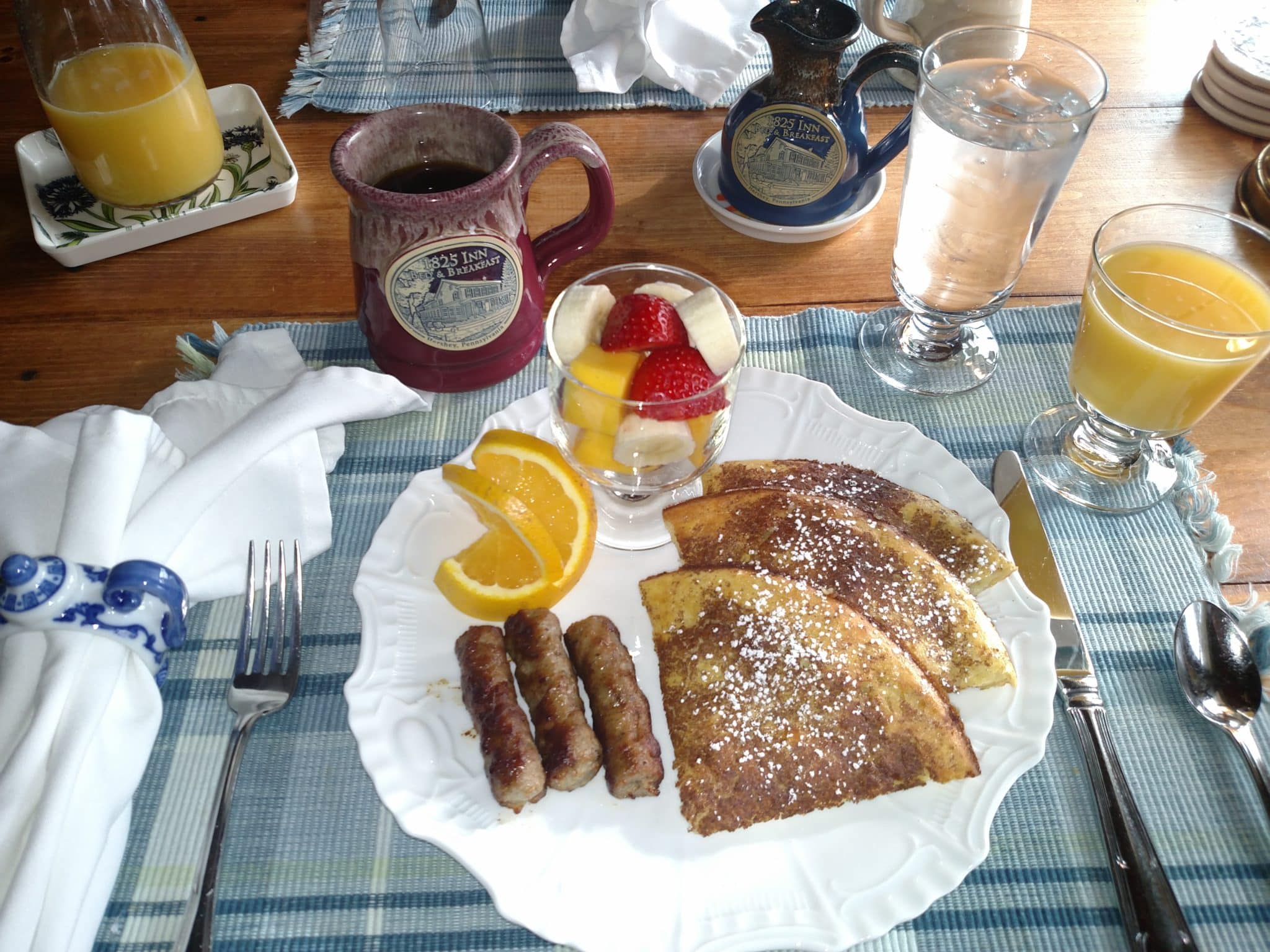 plated breakfast of pancakes, sausage, and fruit