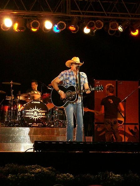 Color photo of Jason Aldean performing on stage with colored lights