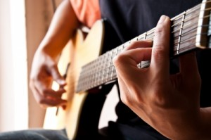 Color photo of man playing guitar