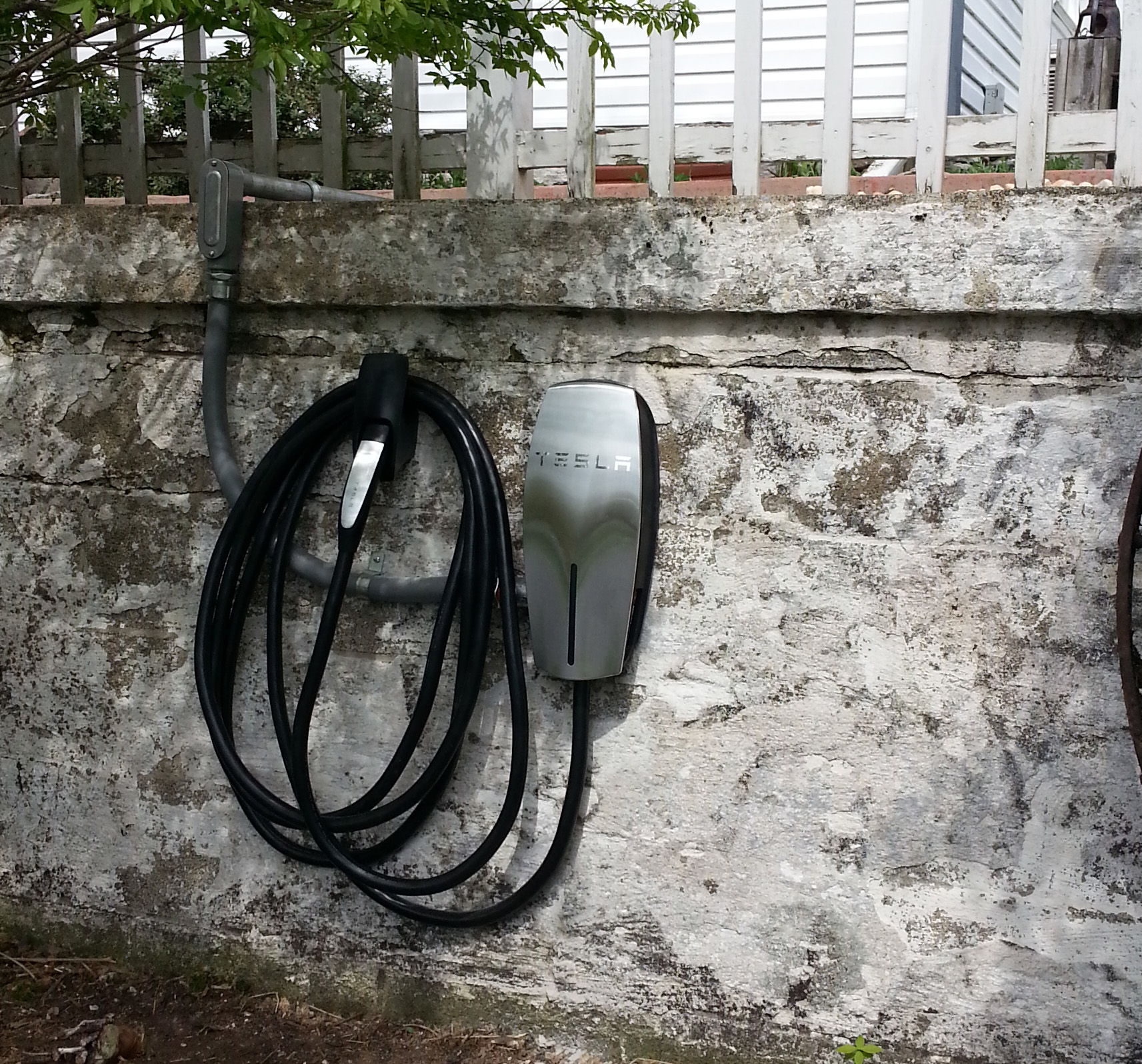 Photo of black Tesla car charger against white stone wall