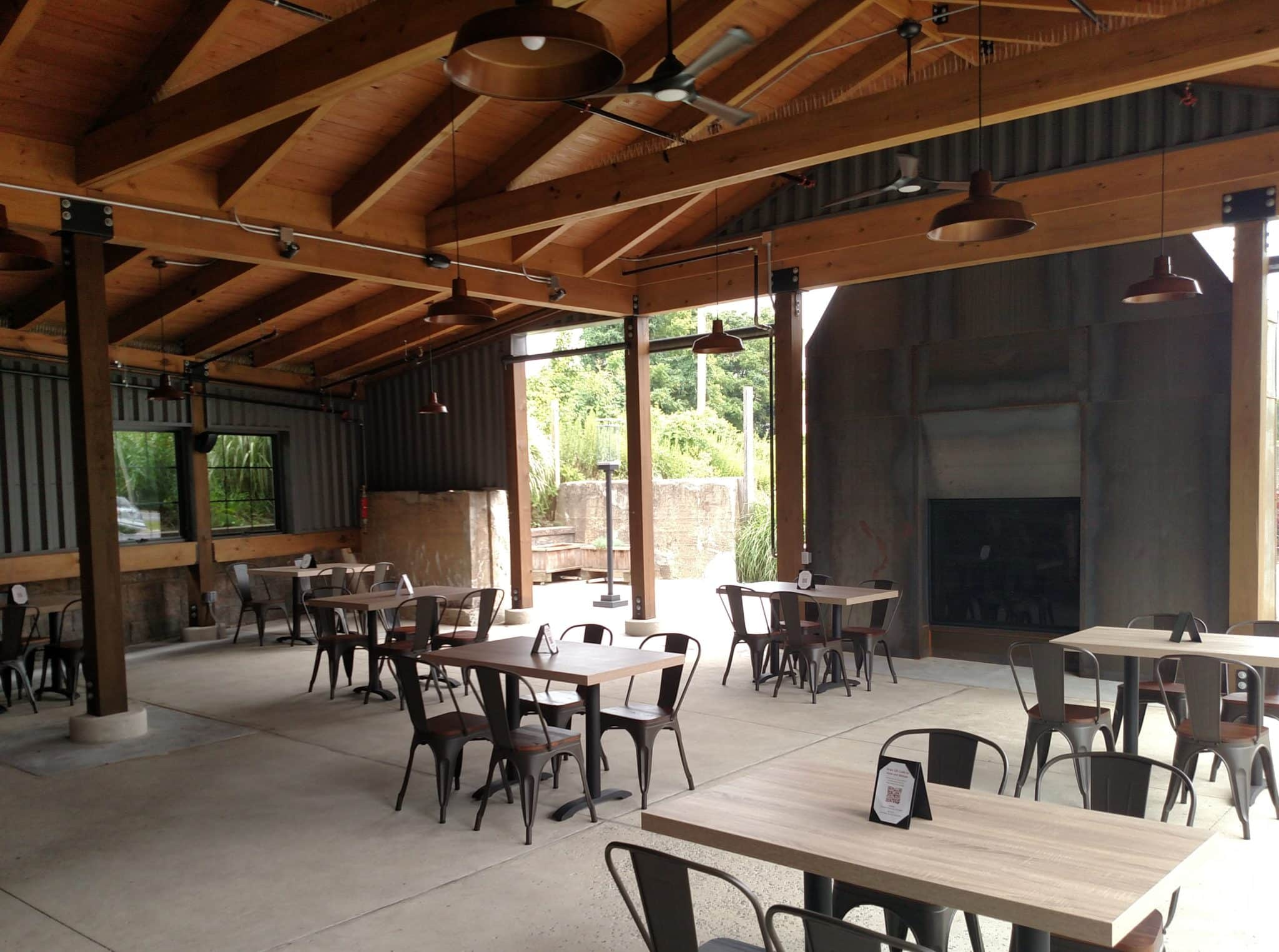outdoor dining area with timber frame roof and fireplace