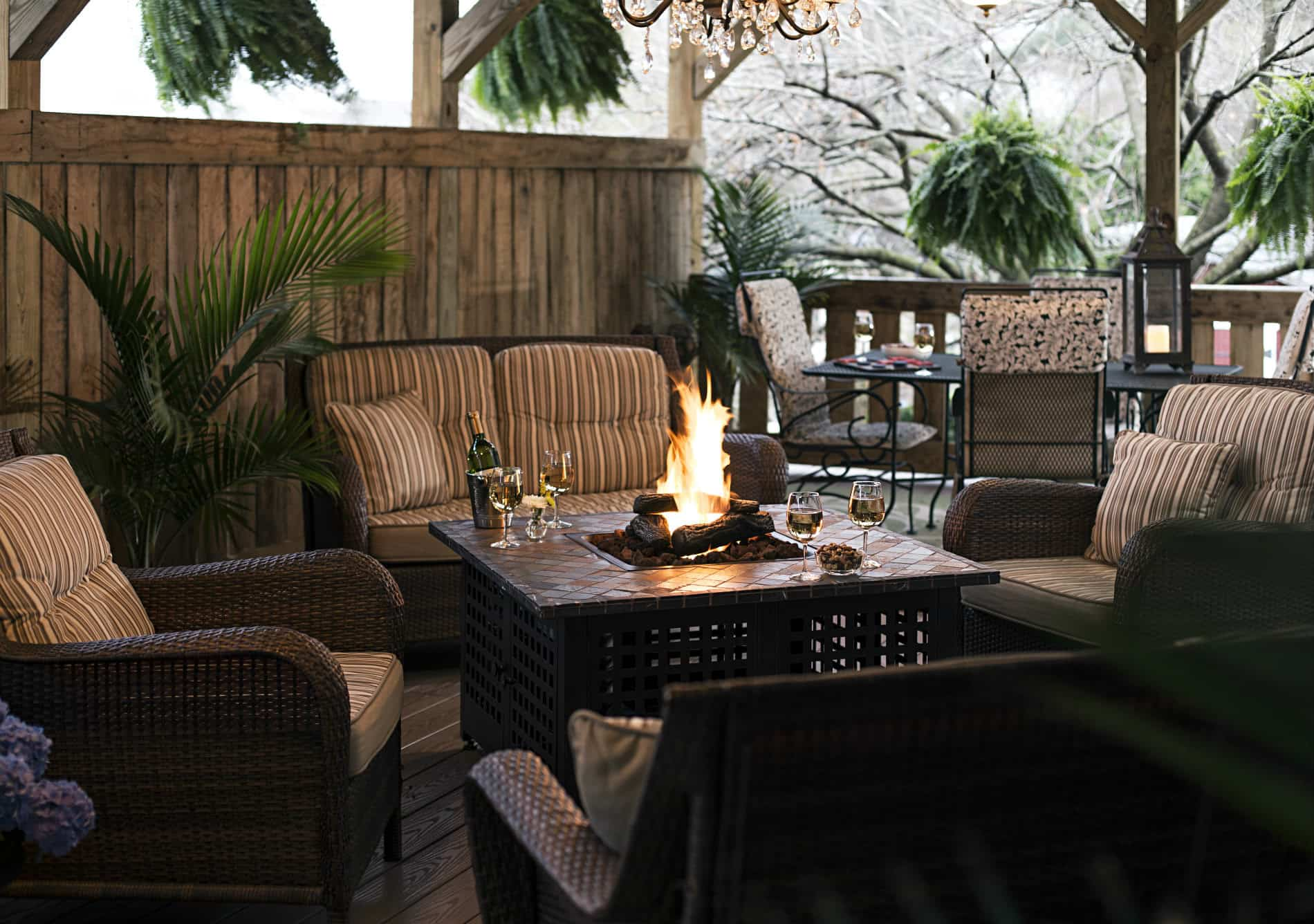 outdoor seating area with brown wicker chairs, fire pit table, wooden pergola and green hanging baskets