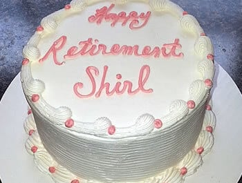 White layer cake with pink accents that reads happy retirement Shirl