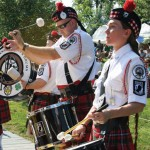 Lady and man dressed in red plaid kilts playing drums