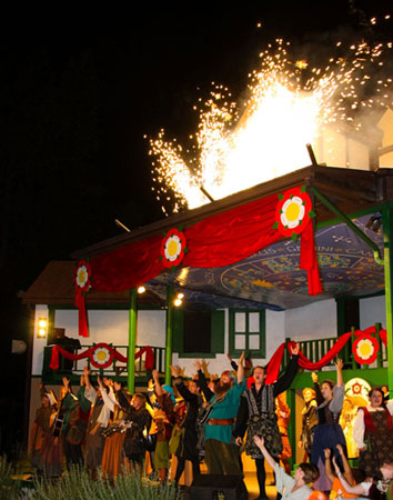 Nighttime photo of the Pennsylvania Renaissance Faire featuring a bright red canopy, fireworks and people