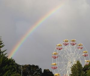 Color photo of a ferris wheel with rainbow and a cloudy sky
