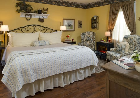 Bed with rod iron headboard with light blue and yellow quilt in a yellow room with brown wood floor