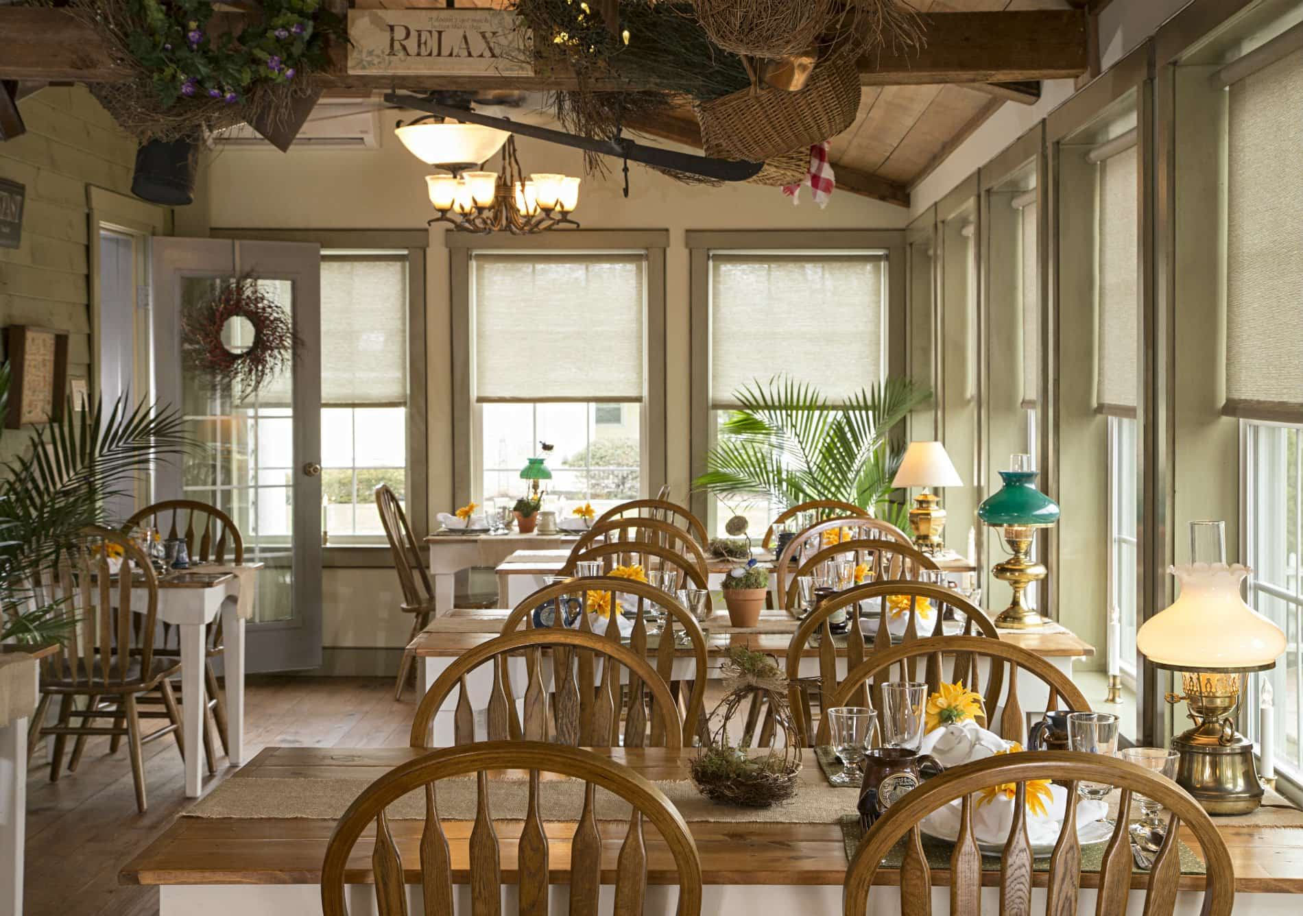 cream colored breakfast room with wooden ceiling beams, 5 white and natural wood tables with white and green oil lamps and yellow flowers