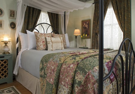 metal canopy bed with a quilted bed spread made of mauve, green, blue, and tan flowers, two nights stands with lamps are beside the bed