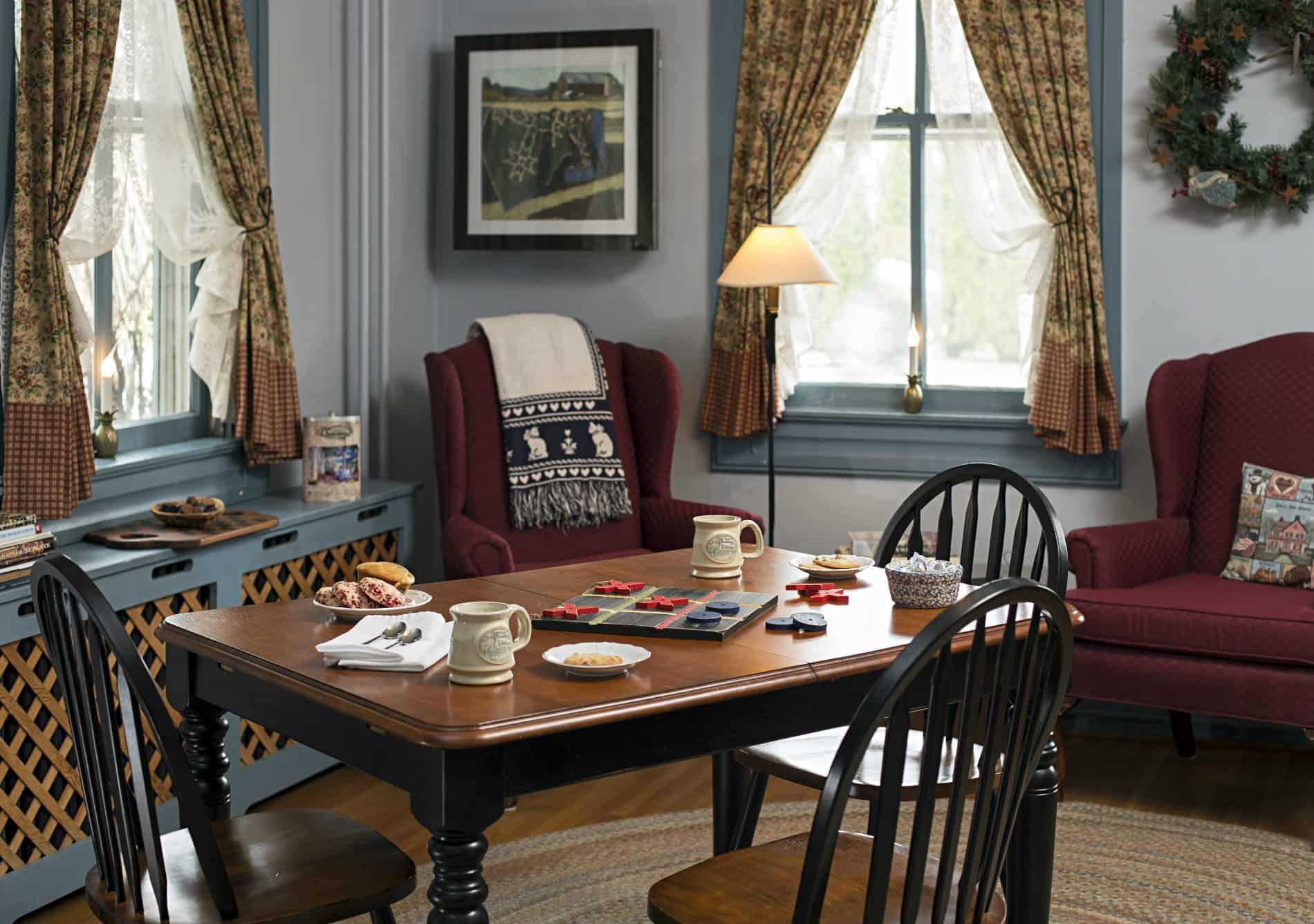Brown and black game table with two coffee mugs and table games in a room with grey walls and blue trim, against the grey wall are two burgandy chairs