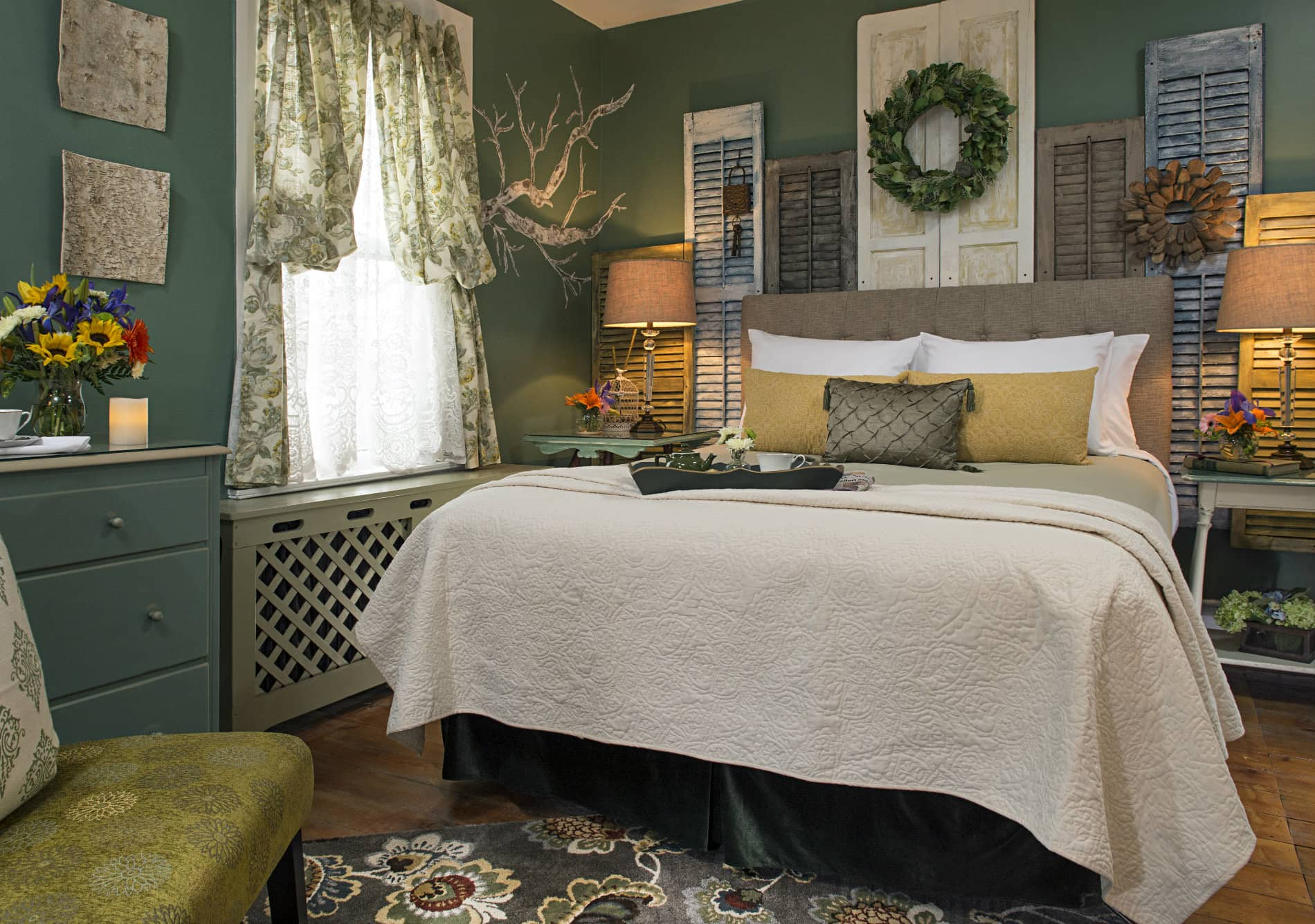green room with bed covered in white and tan linens with golden yellow throw pillows and a decorative display of grey, brown and white window shutters behind the bed