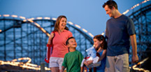 Colorful photo of a family with a roller coaster in the background