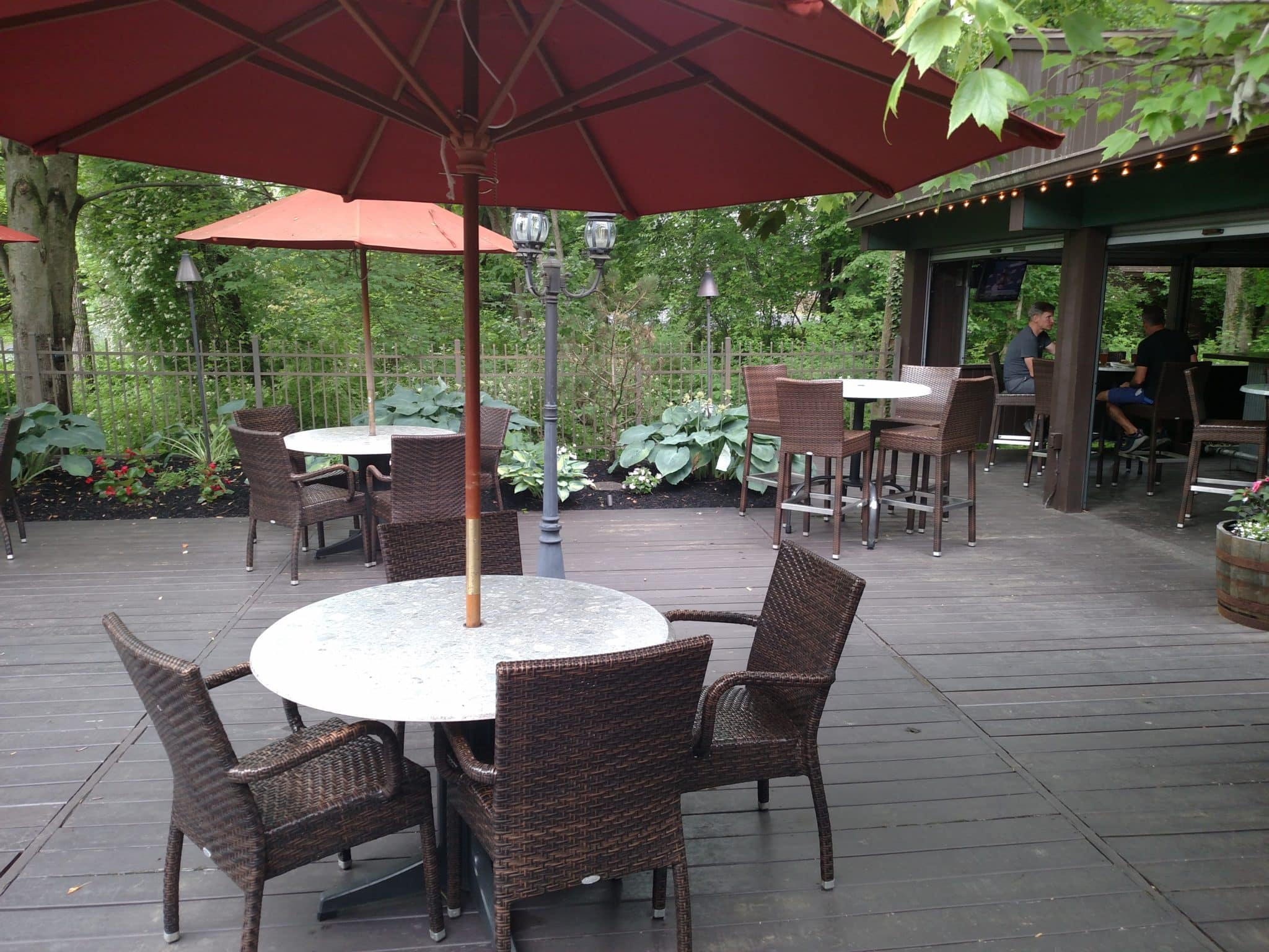 the deck of the hide a way showing covered tables and chairs