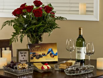 A dark wood table with red roses, Hershe's pot of gold chocolates, bottle of wine with two wine glasses, glass bowls with crackers and chocolates, and 3 candles