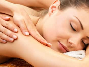 Woman resting head on a white towel getting a massage