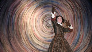Color photo of woman dressed in Victorian era dress with a swirled back drop for Poe Evermore