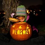 Child peeking into an illuminated orange pumpkin at nighttime