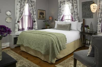 Grey room with bed covered in white linens with green quilt. Two windows by the bed have floral print curtains with purple sheers