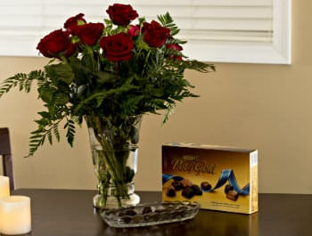 Vase of red roses on a wooden table with chocolates in a glass bown and a brown and gold box of Hershey's chocolates